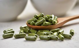 image of laxatives  - Moringa capsule pills in the woodspoon on white wood - JPG