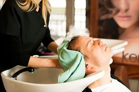picture of beauty parlour  - Female hairdresser washing hair of smiling man client at beauty parlour - JPG