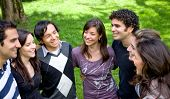 friends or university students smiling outdoors in a park