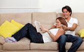 Постер, плакат: Красивая пара смотреть телевизор и читать на диване