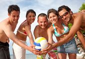 Group of people with a volleyball at the beach