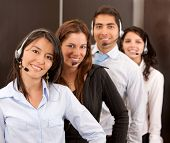 Customer support operators in an office smiling
