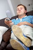 Relaxed man with a remote control watching tv
