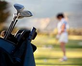 Bag of golf clubs outdoors - female player on the background
