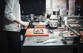 Restaurant Chef Cook Preparing Salmon Filet Flambe. Focus Is On The Salmon, Burner And Cook S Hand.  poster