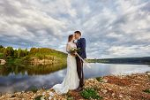 Beautiful Couple In Love Kissing While Standing On Ground By Lake. Wedding Couple At Sunset, Blue Cl poster