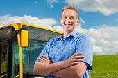 stock photo of bus driver  - Bus driver is standing in front of his bus under al blue sky - JPG