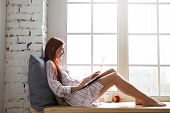 Sideways Shot Of Cheerful Teenage Girl In Striped Shirt Relaxing By Window, Speaking To Friend Via O poster