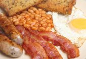 Fried breakfast with egg, bacon, sausages, baked beans and fried bead.