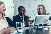 Success Smiling Woman Shows Something On Computer Tablet To Black Businessman At Business Meeting. B poster