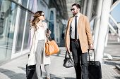 Business Couple In Coats Walking Out The Airport With Luggage During The Business Trip poster