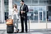 Business Couple In Suits Standing Near The Airport With Luggage During The Business Trip poster