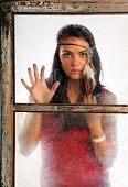 Portrait of beautiful young woman wearing feather headband looking through old window