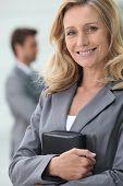 Empresaria sonriente holding organizador personal con colega en fondo