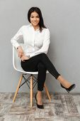 Full length image of happy business woman in formal wear sitting on chair in office isolated over gr poster