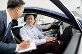 Happy Asian Couple Buying Car In Dealership poster