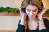 Beautiful Middle Aged Woman In Cafe, Smiling Woman Listening To The Music Via Headphones At A Cafe,  poster