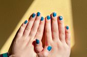 Vibrantly Painted Blue Fingernails In A Line With Interlocking Thumbs poster