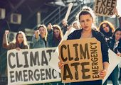 Young Woman With Poster In Front Of People Protesting About Climate Changing On The Street. Meeting  poster