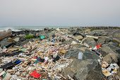 Spilled Garbage On The Beach Near The Big City. Empty Used Dirty Plastic Bottles And Other Garbage.  poster