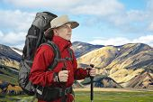 Equipped With Traveler In A Red Jacket With Hiking Poles Looks Into The Distance. Beautiful And Colo poster