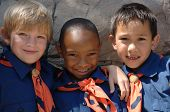 stock photo of boy scouts  - Three boys of diverse ethnic background in cub scout uniforms - JPG