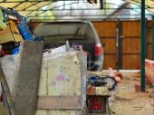 A Garage Or Yard Refurbishment And A Stack Of Unwanted Stuff In The Foreground poster