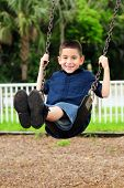 picture of swingset  - Happy young boy sitting swinging on swing at outdoor park