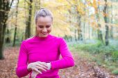 Woman Exercising In Autumn Woodland Looking At Activity Tracker On Smart Watch poster