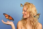 Frau mit vielen Schmetterlingen In der Hand und ihr Haar
