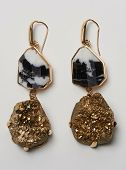 Elegant Loop Earrings With Black Marble And Golden Stone At Bottom With White Background poster
