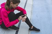 High Angle View Of Young Adult Sportswoman Using Smart Watch Or Fitness Tracker, Resting After Sport poster