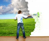 stock photo of wall cloud  - Young couple with paint brushes drawing on the wall - JPG