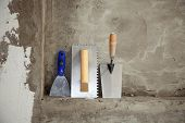 construction stainless steel trowel tools and spatula on cement mortar wall