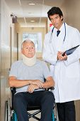 image of neck brace  - Young doctor writing on clipboard by senior man sitting on wheel chair with neck brace - JPG