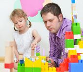 Father And Daughter Playing With Coloured Blocks.