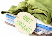 stock photo of naturalist  - stack of multicolored clothing with organic label - JPG