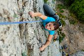 stock photo of daring  - Woman practices in climbing at the rock in the Crimea mountains - JPG