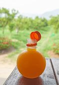 Orange Juice In Bottle On The Wood Table With Green Background.
