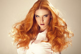 stock photo of terrific  - Portrait of red hair beautiful woman looking at camera - JPG