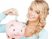 buisness, banking and savings concept - happy businesswoman puts cash money into big piggy bank