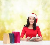 christmas, x-mas, online shopping and electronics concept - smiling woman in santa helper hat with s
