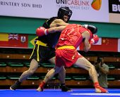 KUALA LUMPUR - NOV 03: Iraq's Husam Mohammed (black) trades pinches with Russia's Magomedov Ali (red) in the Sanda event, 12th World Wushu Championship on November 03, 2013 in Kuala Lumpur, Malaysia.