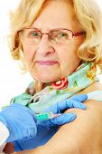 A portrait of a senior woman being given a shot in the arm