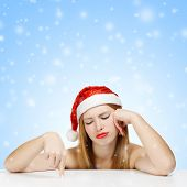 Young Woman In Santa Claus Hat Posing With Wearied Look On Blue Background With Falling Snow