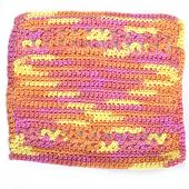 Handmade crocheted dishcloth made with different stitches and multicolored yarn.