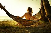 Young lady relaxing in the hammock on the tropical beach and enjoying sea view