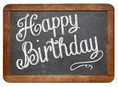 Happy Birthday  - white chalk text  on a vintage slate blackboard isolated on white
