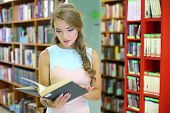 A young woman is looking surprised into a book among the bookshelves in the library