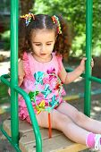Little girl with tails sitting on a swing and looks at the whirligig